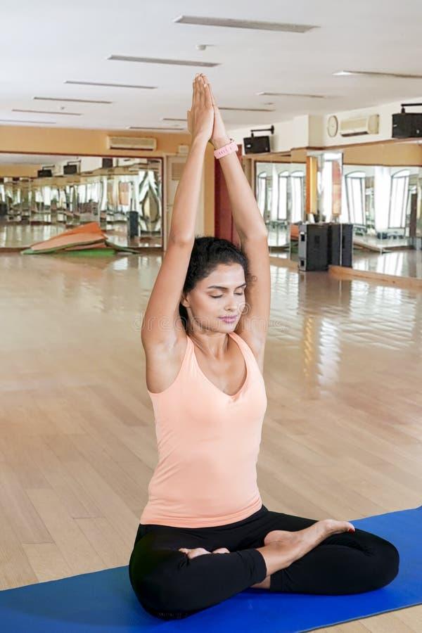 Kędzierzawego włosy kobieta robi joga pozom w sprawności fizycznej centrum obrazy stock
