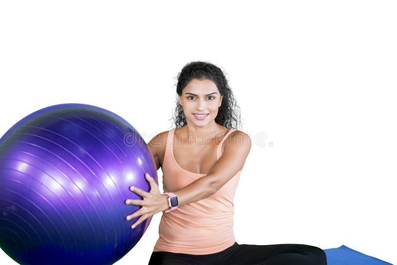 Kędzierzawego włosy kobieta trzyma joga balowy na studiu fotografia stock