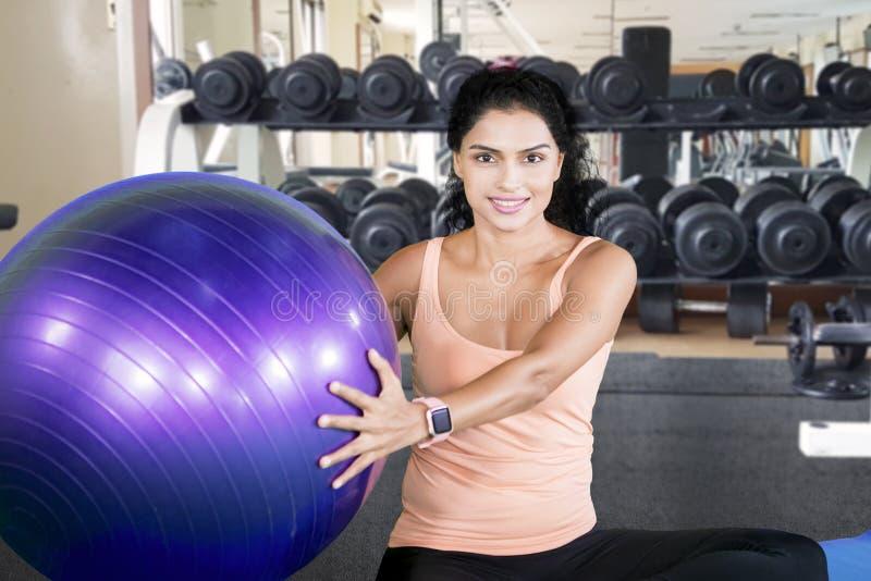 Kędzierzawego włosy kobieta trzyma piłkę w sprawności fizycznej centrum fotografia royalty free