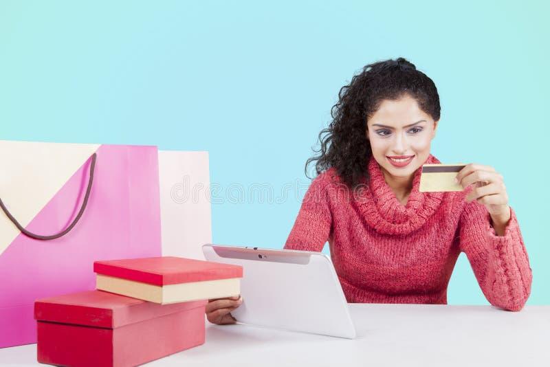 Kędzierzawego włosy kobieta używa pastylkę i kartę kredytową fotografia royalty free