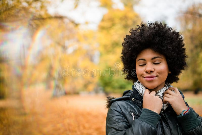 Kędzierzawego włosy kobieta z zamkniętymi oczami w parku zdjęcia royalty free