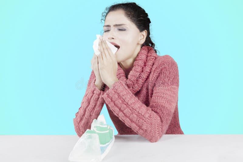 Kędzierzawego włosy kobiety kichnięcie z tkanką na studiu zdjęcia stock