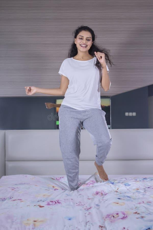 Kędzierzawego włosy kobiety taniec na łóżku obraz stock