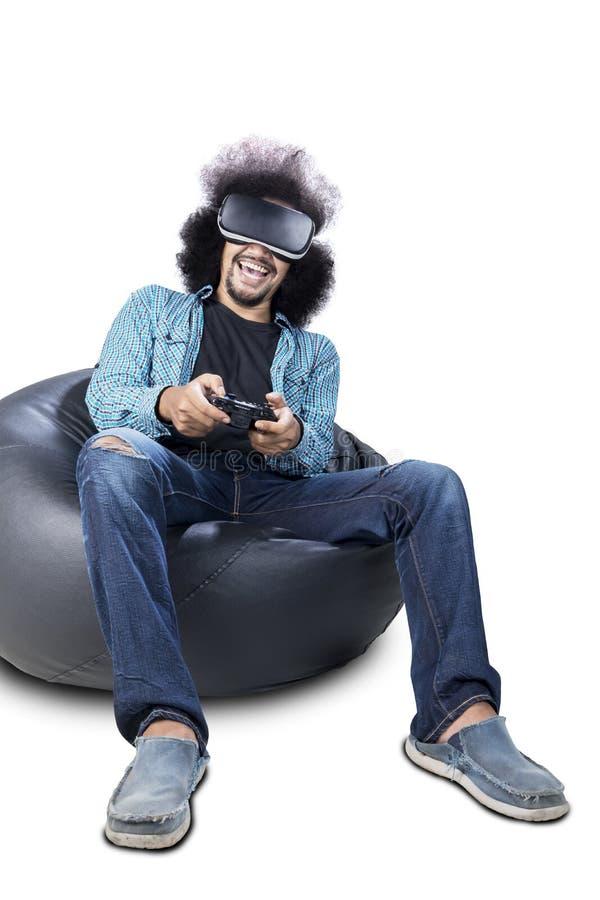 Kędzierzawego włosy mężczyzna bawić się gra wideo z VR szkłami zdjęcia royalty free