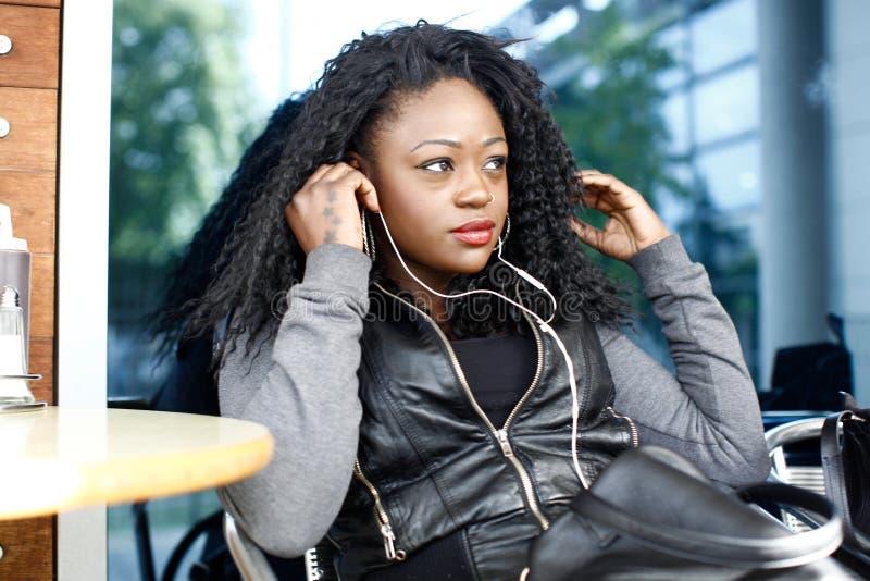 Kędzierzawej murzynki Słuchający Muzyczny Używa hełmofon fotografia royalty free