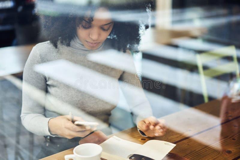 Kędzierzawy afroamerykanin w szarej kurtce używać smartphone i radia związek zdjęcie royalty free