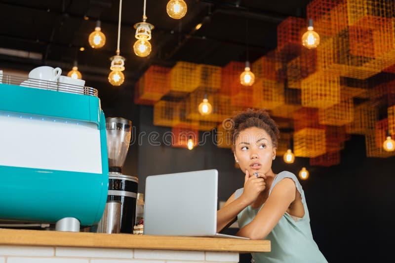 Kędzierzawy ciemnowłosy kobiety czuć rozważny podczas gdy robić odległej pracie obrazy stock