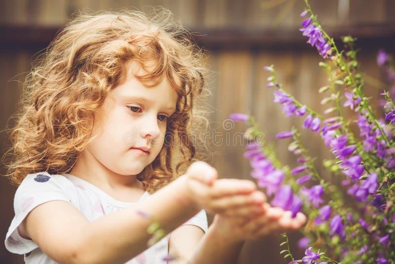 Kędzierzawy dziecko z kwiatami w ona ręka Tonowanie fotografia Instagram fil zdjęcia stock