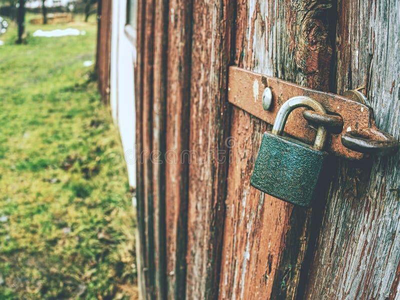Kłódka na drewnianych bramach tapicerować z żelazem fotografia stock