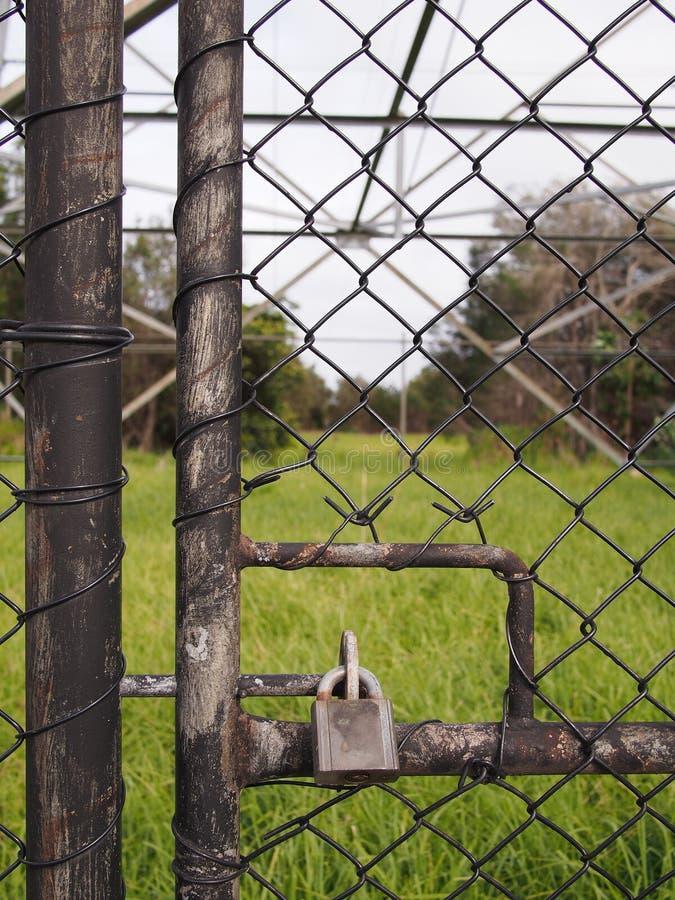 Kłódka na drucianym ogrodzenia ochronnego drzwi przed wysokim woltaż władzy słupem obrazy royalty free