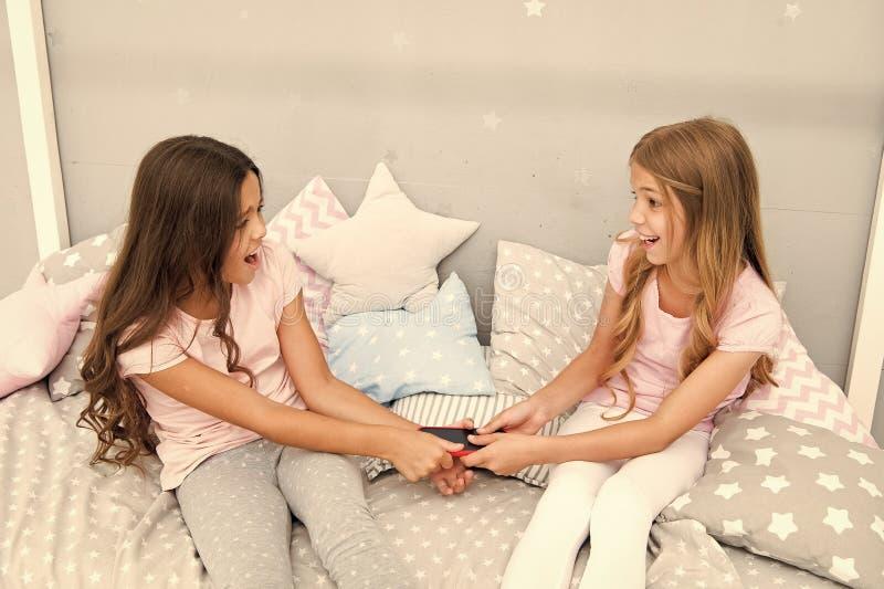 Kłótnia między siostrami nie udostępniaj telefonu czas telefonu przed uśnięciem stosunki rodzinne siostry używają telefonu w łóżk fotografia royalty free