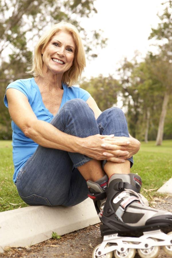 kładzenie kreskowy parkowy senior jeździć na łyżwach kobiety zdjęcia stock