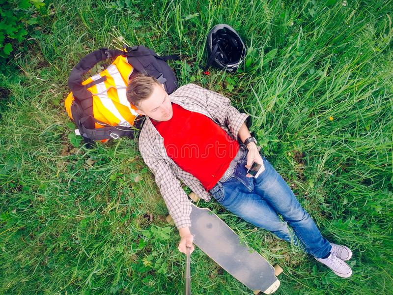 Kłamający w trawie facet jest odpoczynkowy po jechać longboard obrazy royalty free
