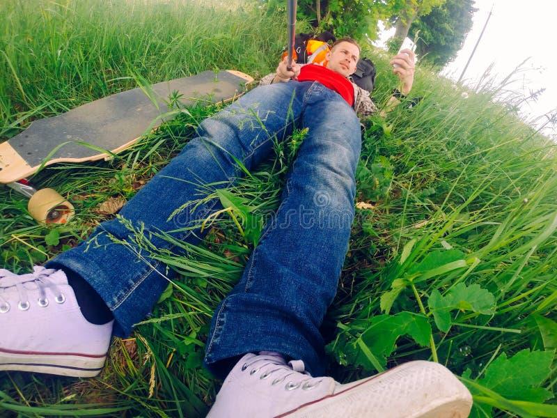 Kłamający w trawie facet jest odpoczynkowy po jechać longboard obraz stock