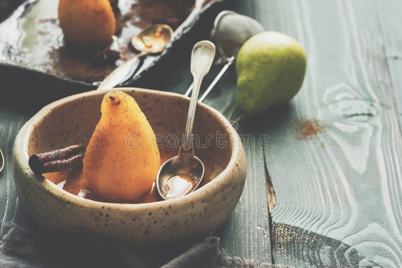 Kłusująca bonkreta w syropie w ceramicznym pucharze na nieociosanym drewnianym stole Zimy i jesieni smakowity deser Selekcyjna os fotografia stock