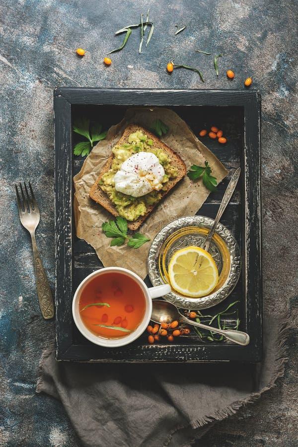 Kłusujący jajko, avocado kanapka i cytryny herbata na czarnej drewnianej nieociosanej tacy, Świeży śniadaniowy widok z góry, mies fotografia royalty free