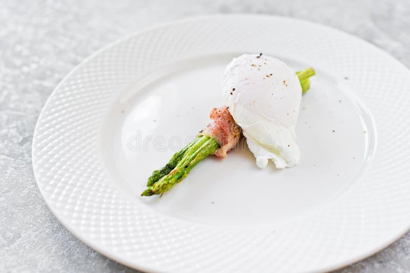 Kłusujący jajko na piec asparagusie zawijającym w bekonie Szary t?o, boczny widok obraz royalty free