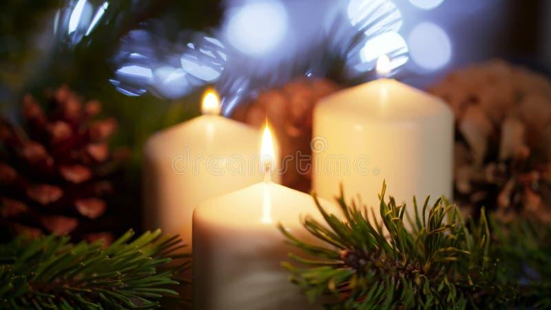 4K被点燃的蜡烛尼斯长的特写镜头与圣诞节装饰品的在慢动作 免版税库存照片
