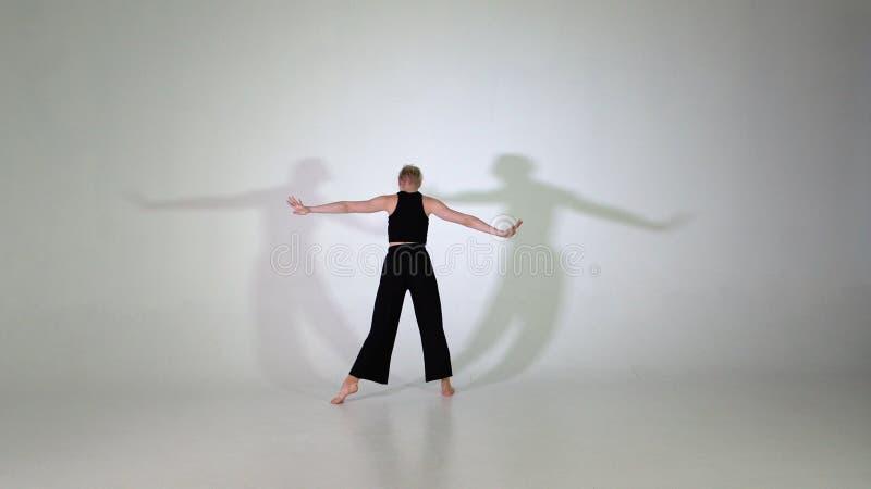 4K - Όμορφο εύκαμπτο νέο κορίτσι που κάνει κάνοντας τις ακροβατικές ασκήσεις στοκ εικόνα