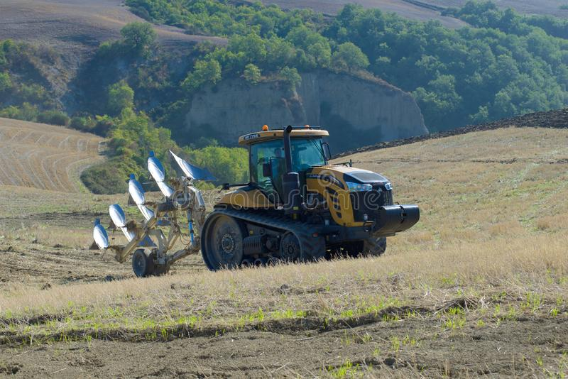 2K11 отслеживало претендента MT775E трактора с плужком на холмах Тосканы на солнечный день осени стоковые изображения rf