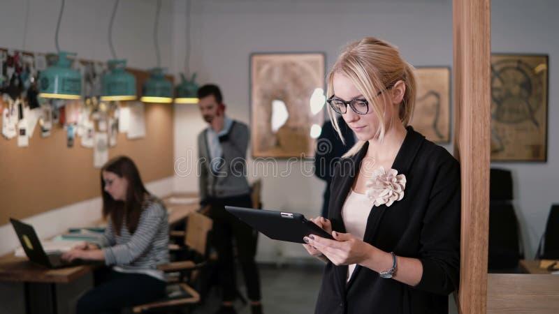 4K 特写镜头年轻美丽的白肤金发的女实业家在现代起始的办公室使用触摸屏幕片剂 免版税库存图片