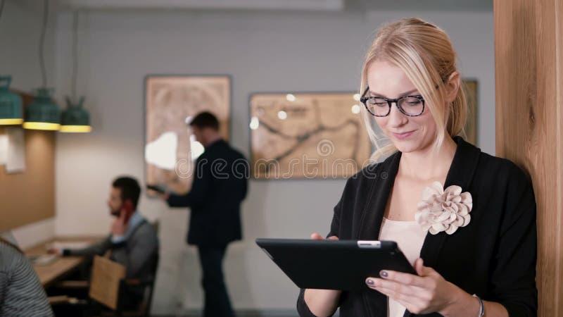 4K 年轻美丽的白肤金发的女实业家在现代起始的办公室使用触摸屏幕片剂 免版税库存图片