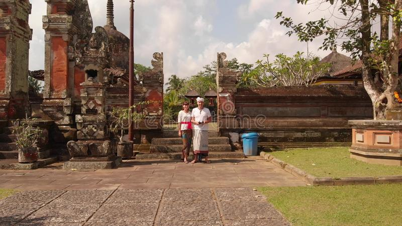 4K aerial flying drone video of european tourist in traditional clothes in the balinese temple. stock photos