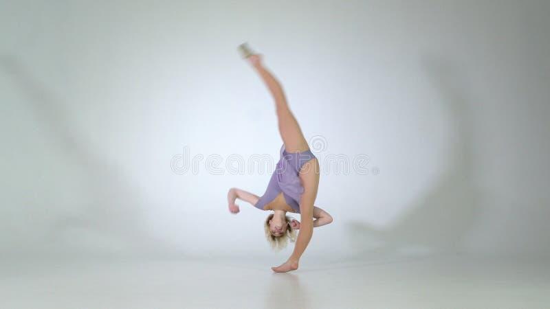 4k - Böjlig dansare som ler och gör benförlängning i studio royaltyfria bilder