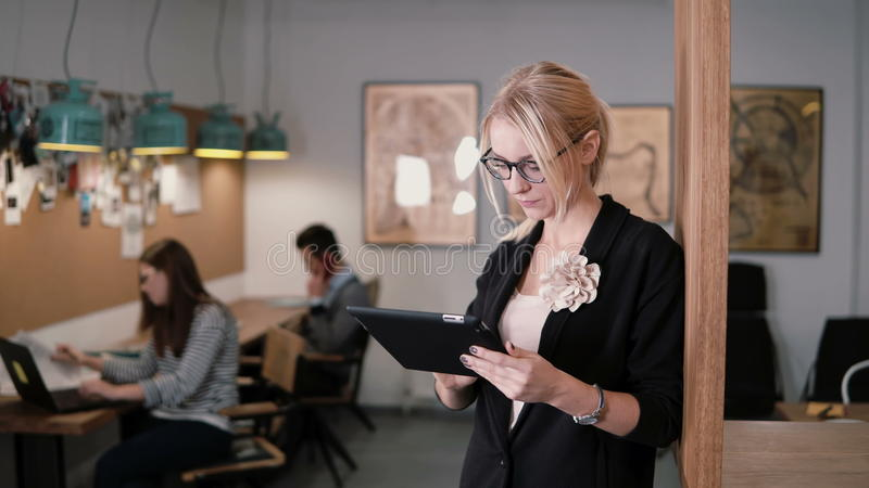 4K de jonge mooie blondeonderneemster gebruikt een touchscreen tablet in het moderne startbureau royalty-vrije stock foto's