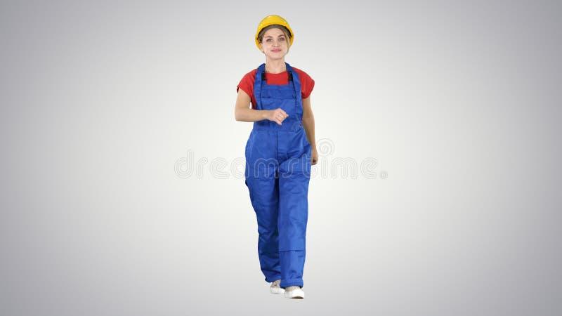 走与意志的确信的老练的女监工在梯度背景工作 库存图片