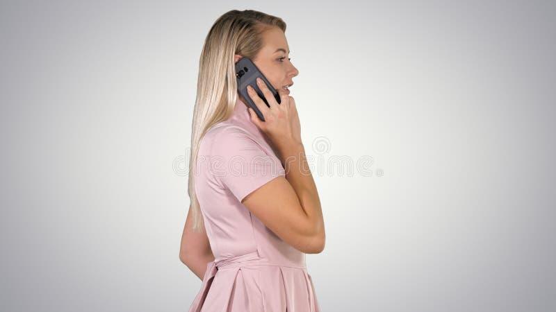 Молодая дама имея звонок на предпосылке градиента стоковое изображение