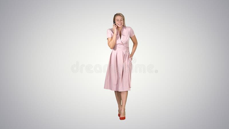 Счастливая усмехаясь женщина говоря на сотовом телефоне пока идущ на предпосылку градиента стоковые фотографии rf