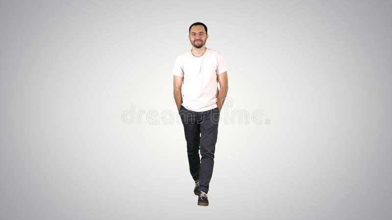 确信的年轻成人人走的前锋和看在梯度衬衣的照相机在梯度背景 免版税库存照片