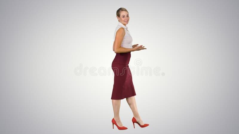 Бизнес-леди сильно идя вперед и говоря к камере на предпосылке градиента стоковая фотография rf