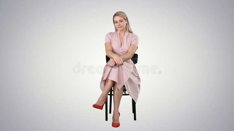 美丽的年轻女人,女孩,有坐椅子和看对照相机的长发的式样金发碧眼的女人在梯度背景 库存照片
