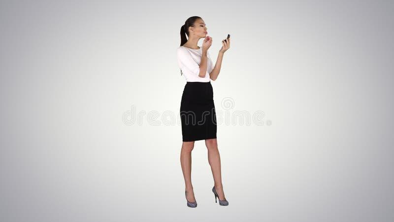 美女,洗染她的嘴唇唇膏桃红色,看在梯度背景的镜子 免版税库存照片