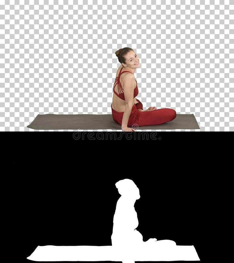 运动的女子实践的瑜伽莲花姿势,转向照相机和微笑,阿尔法通道 免版税库存照片