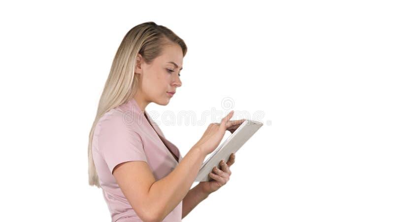 拿着数字片剂的女孩搜寻某事在白色背景 免版税库存图片
