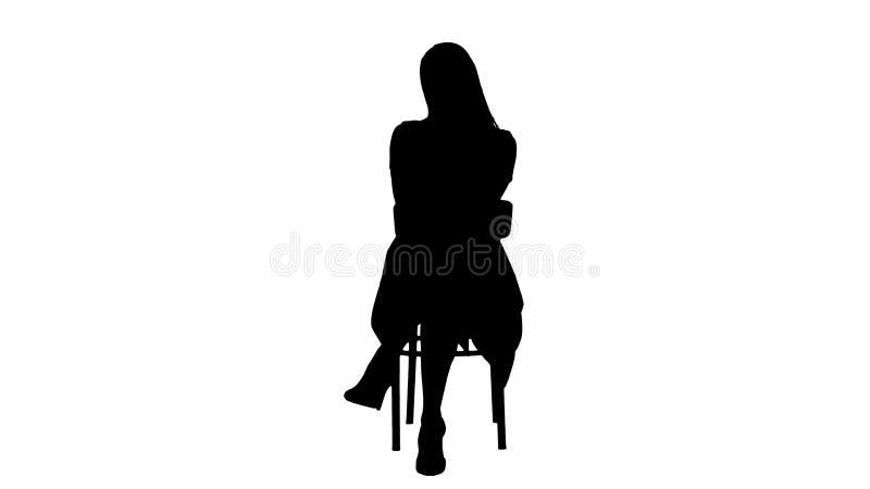 剪影美丽的年轻女人,女孩,有坐椅子和看对照相机的长发的式样金发碧眼的女人 免版税库存图片