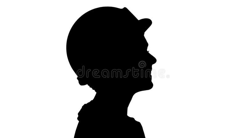 现出轮廓有黄色安全帽的微笑年轻女人的工程师走和 免版税库存图片