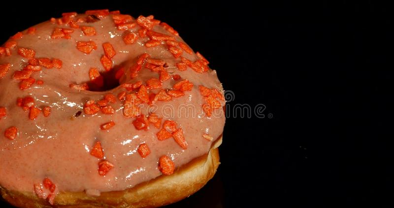 4K footage of glazed sweet donut with sprinkles, rotating with normal speed, isolated on black background.  royalty free stock photo