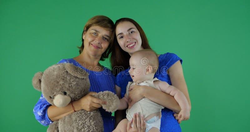 4k - glückliche Familie von Generation 3 der Frau auf grünem Schirm stockfotos
