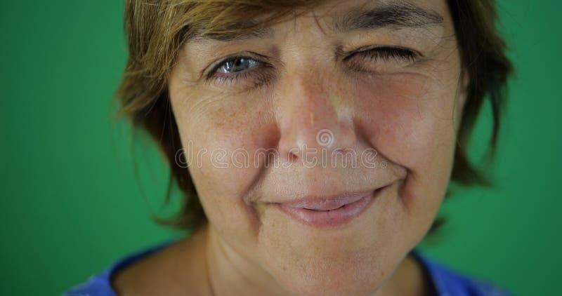 4k - Mulher de meia idade com piscadelas curtos e sorrisos de um corte de cabelo no verde imagem de stock