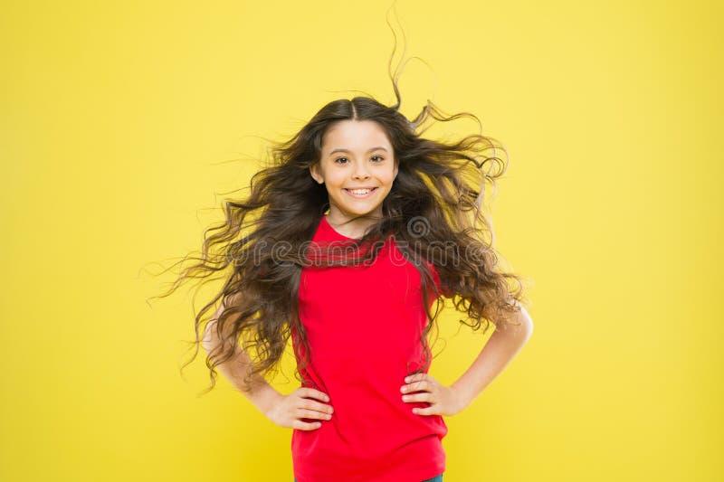 K?nnande bra sagolikt h?r Förtjusande liten flicka som ler med långt brunetthår Lyckligt barn med flödande hår på guling royaltyfria bilder