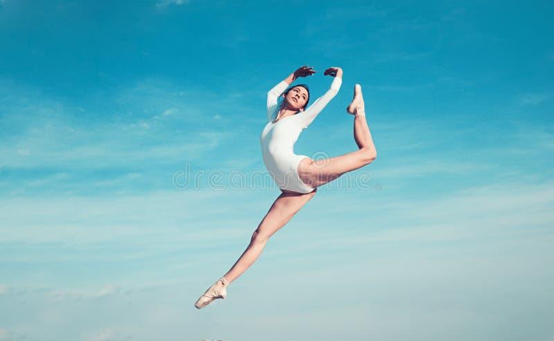 K?nner sig som flyg Ung ballerina som hoppar p? bl? himmel N?tt flicka i danskl?der gullig dansare f?r balett konsert royaltyfria foton