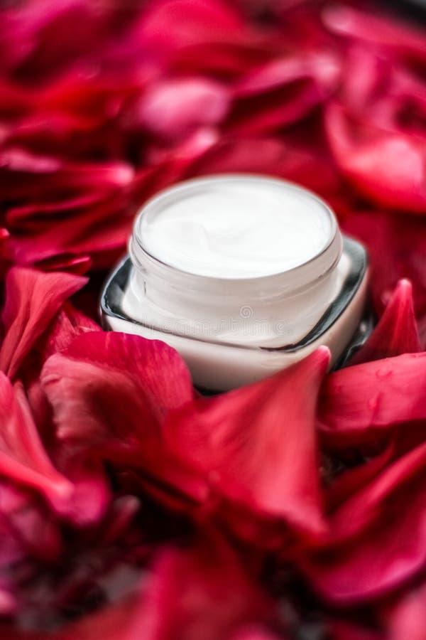 K?nslig skincarefuktighetsbevarande hudkr?mkr?m p? r?da blommakronblad och vattenbakgrund, naturvetenskap f?r hud fotografering för bildbyråer
