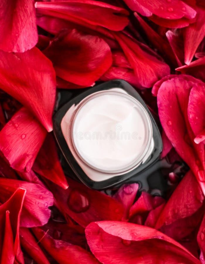 K?nslig skincarefuktighetsbevarande hudkr?mkr?m p? r?da blommakronblad och vattenbakgrund, naturvetenskap f?r hud royaltyfri foto