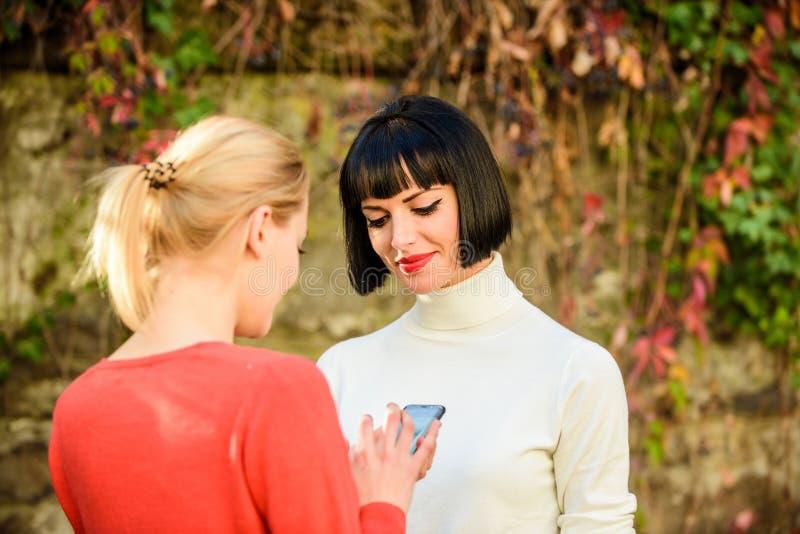 K?p direktanslutet Två kvinnor med smartphonen som utomhus meddelar Samkv?mmen knyter kontakt begrepp Dela sammanlänkning modern  arkivbild