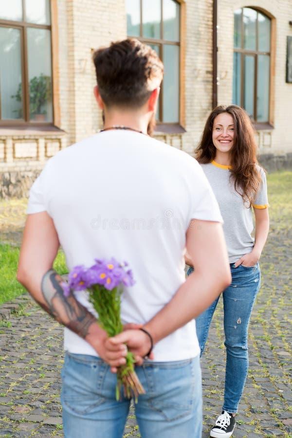 k?rlekshistoria f?r tr?dg?rds- flicka f?r pojke kyssande Blommar leveransbegrepp Selektivt fokusera f?rbunden f?r?lskelse förbere fotografering för bildbyråer