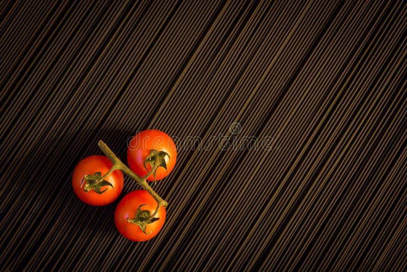 K?rsb?rsr?d tomat och r? svart pasta arkivbild